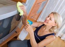Mulher que limpa a tevê com o pano Foto de Stock Royalty Free