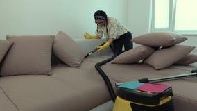 Mulher que limpa um sofá com um aspirador de p30 e que verifica a pressão do vácuo filme