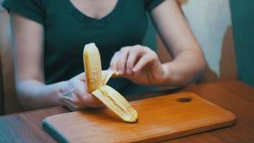 Mulher que limpa uma banana ao sentar-se em uma tabela em uma cozinha home video estoque
