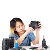 Mulher que limpa uma câmera com o pano e o equipamento da fotografia imagens de stock royalty free