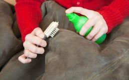 A mulher que limpa uma pele de carneiro com whisk a vassoura fotografia de stock