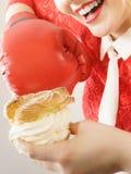 Mulher que luta fora o alimento mau, bolo de encaixotamento do sopro de creme Foto de Stock