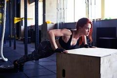 A mulher que magro nova da aptidão fazer empurra levanta na caixa de madeira Fotografia de Stock