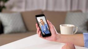 Mulher que manda o vídeo chamar em casa o smartphone video estoque