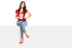 Mulher que mantém a caixa da pipoca assentada em um painel Imagem de Stock
