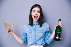 Mulher que mantém dois de vidro e a garrafa do champanhe Fotos de Stock