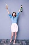 Mulher que mantém dois de vidro e a garrafa do champanhe Imagem de Stock Royalty Free