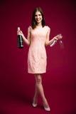 Mulher que mantém dois de vidro e a garrafa do champanhe Fotos de Stock Royalty Free