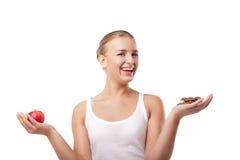 Mulher que mantém a maçã e o chocolate isolados Fotografia de Stock