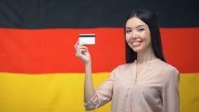 Mulher que mantém o cartão de crédito contra a bandeira alemão, transferência de dinheiro internacional filme