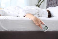 Mulher que mantém o condicionador de ar de controle remoto na cama disponível fotos de stock