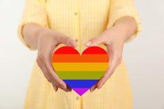 Mulher que mantém o coração pintado em cores da bandeira de LGBT imagens de stock