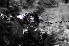 Mulher que mantém o fio e a flor da farpa disponivéis conceito do abuso fotografia de stock royalty free
