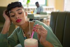 Mulher que mantém sua cabeça disponível ao olhar o milk shake foto de stock royalty free