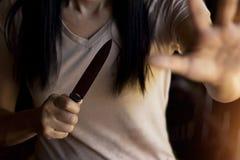 Mulher que mantém uma faca disponivel ao defender-se imagens de stock
