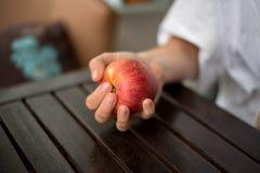 Mulher que mantém uma maçã disponivel imagem de stock