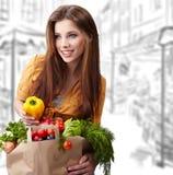 Mulher que mantem um saco cheio do alimento saudável Fotografia de Stock