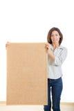 Mulher que mantém uma cortiça da placa de madeira isolada no fundo branco Imagem de Stock