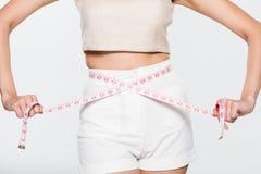 Mulher que mede sua cintura imagens de stock royalty free