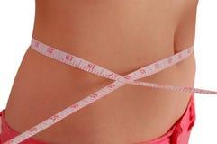 Mulher que mede sua cintura com uma fita de medição Imagens de Stock