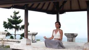 Mulher que medita e que faz a ioga no templo abandonado Pose praticando fêmea filme