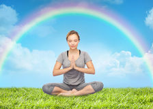 Mulher que medita na pose da ioga dos lótus sobre o arco-íris Fotos de Stock Royalty Free