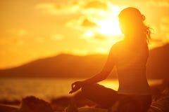 Mulher que medita na pose dos lótus na praia no por do sol fotos de stock royalty free