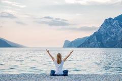 Mulher que medita no lago fotos de stock royalty free