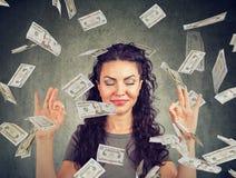 Mulher que medita sob a chuva do dinheiro fotos de stock royalty free