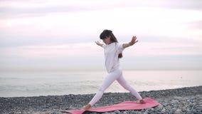 Mulher que medita sobre a praia no amanhecer vídeos de arquivo