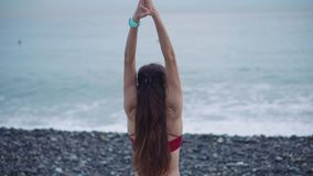 Mulher que medita sobre uma posição da praia vídeos de arquivo