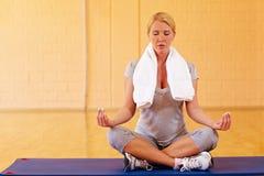 Mulher que meditating na ginástica Fotografia de Stock Royalty Free