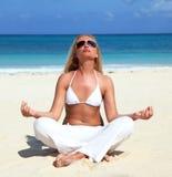Mulher que meditating na praia Fotografia de Stock Royalty Free