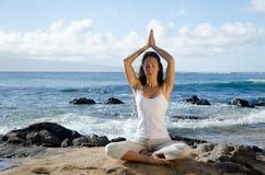 Mulher que Meditating na praia Fotos de Stock