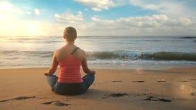 Mulher que meditating na praia video estoque
