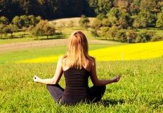 Mulher que meditating no campo Imagem de Stock Royalty Free