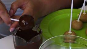 Mulher que mergulha o bolo do popcake no chocolate preto Em seguida na tabela est?o as placas para PNF do bolo video estoque
