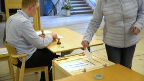 Mulher que molda um voto na urna de voto durante eleições