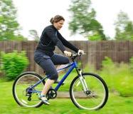 Mulher que monta a bicicleta Fotografia de Stock