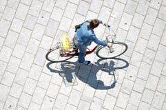 Mulher que monta sua bicicleta Imagens de Stock