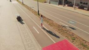 Mulher que monta um ar livre do 'trotinette' no verão Tiro a?reo video estoque