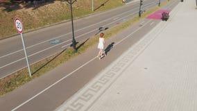 Mulher que monta um ar livre do 'trotinette' no verão Tiro a?reo vídeos de arquivo