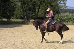 Mulher que monta um cavalo imagem de stock