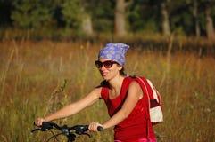 Mulher que monta uma bicicleta Imagem de Stock Royalty Free