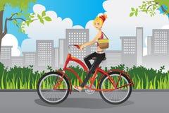 Mulher que monta uma bicicleta Fotografia de Stock