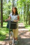 Mulher que monta uma bicicleta com seu cão Imagens de Stock Royalty Free