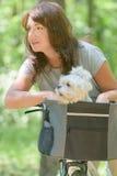 Mulher que monta uma bicicleta com seu cão Foto de Stock