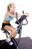 Mulher que monta uma bicicleta de exercícios Fotos de Stock Royalty Free