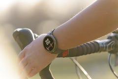 Mulher que monta uma bicicleta e que usa o smartwatch imagens de stock royalty free
