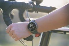 Mulher que monta uma bicicleta e que usa o smartwatch foto de stock royalty free
